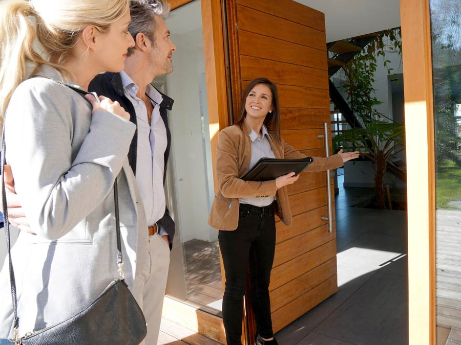 Female real estate agent leading a couple to view a home for sale