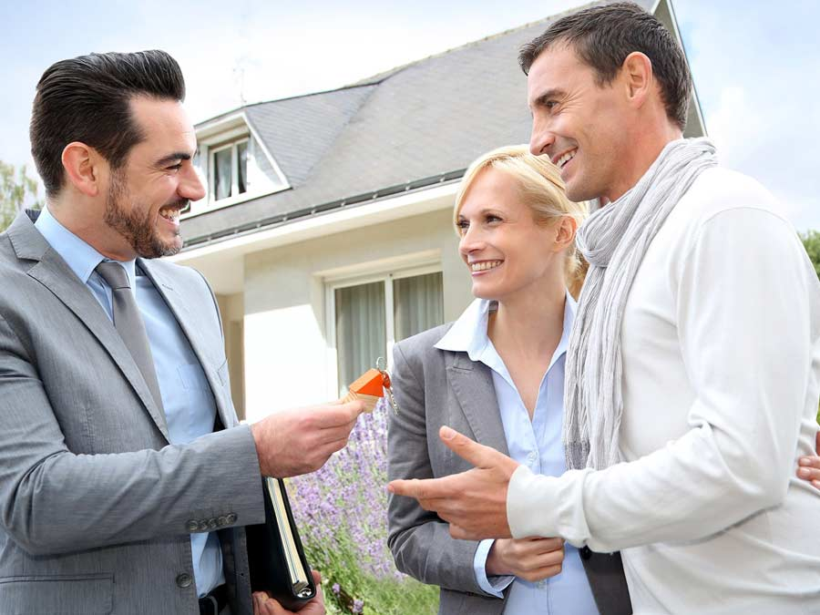 Real estate agent giving keys to a new home to a happy couple