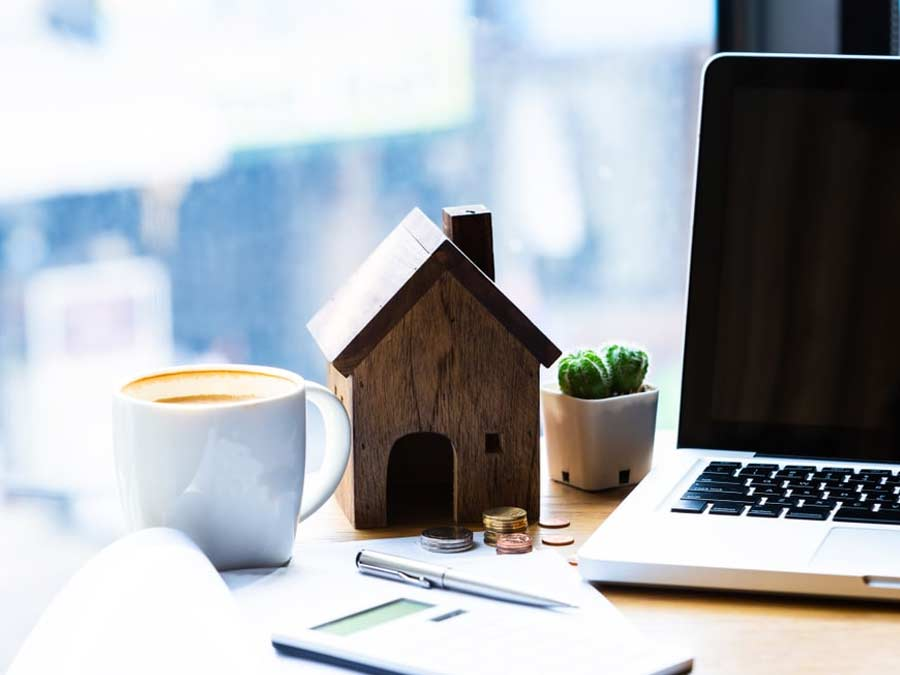 Small wooden house on a desk next to a laptop and a cup of coffee