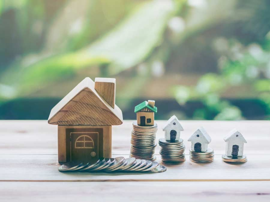 Small wooden block houses on top of piles of coins