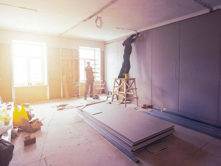Two workers putting up new drywall in a home