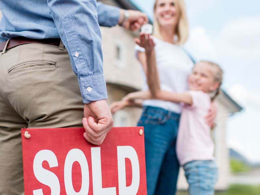 Real Estate Agent holding a sold sign handing keys to a mother and daughter